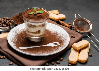 Classic tiramisu dessert in a glass and cup of coffee on dark concrete background