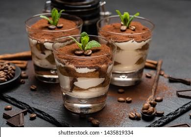 Klassischer Tiramisu-Dessert auf dunklem Betonhintergrund in einem Glas auf Stein