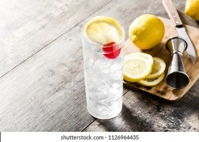 Classic Tom Collins cocktail on wooden table. Copyspace