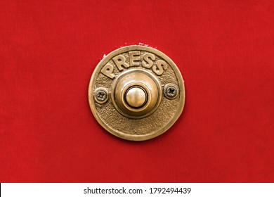 Classic traditional rustic heavy cast brass doorbell button on a seamless red wall shot straight on.