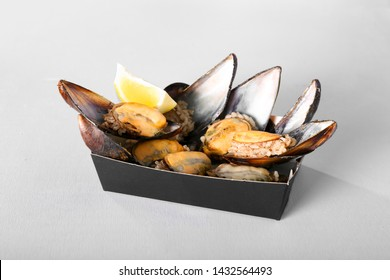 Classic Turkish Delicious Rice Stuffed Mussels isolated on grey background. Take away street food concept.