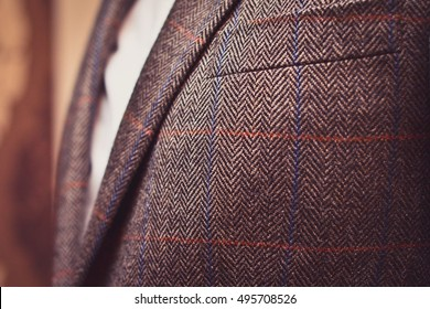 Classic tweed men's jacket with closeup on wool fabric texture. Fashion and lifestyle. Portrait of a buisinessman in a jacket. Copy space.