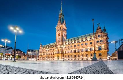 Classic twilight view of famous Hamburg city hall with Rathausmarkt square illuminated during blue hour at dusk, Hamburg, Germany