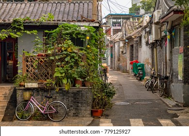 Classic Typical Street Scene in Beijing China, View of Residential Hutong (Narrow Alley) with Bicycles, Shops, and Plants.