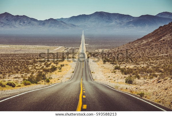 Classic vertical panorama view of an endless straight road running through the barren scenery of the American Southwest with extreme heat haze on a beautiful hot sunny day with blue sky in summer