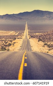 Classic vertical view of an endless straight road running through the barren scenery of famous Death Valley with extreme heat haze on a beautiful sunny day with blue sky in summer, California, USA