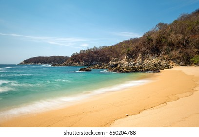 The classic view of a bay and beach in the Huatulco tourist resort by the Pacific Ocean during daytime in the state of Oaxaca, Mexico.