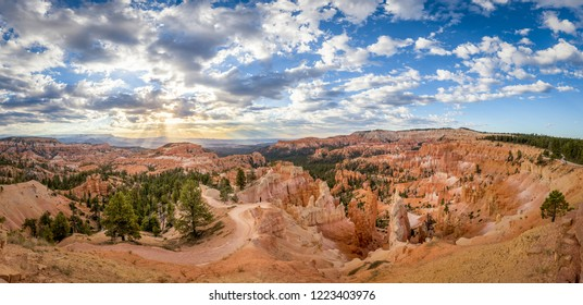 Classic view of Bryce Canyon National Park in beautiful golden morning light at sunrise with blue sky and dramatic clouds as seen from famous Sunrise Point in summer, Utah, American Southwest, USA