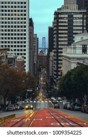 Classic view of California street with cable car railway in financial downtown district and Bay bridge in San Francisco, California, USA. City-scape concept Vintage theme.