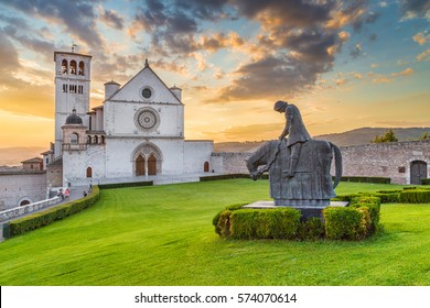 Classic view of famous Basilica of St. Francis of Assisi (Basilica Papale di San Francesco) in beautiful golden evening light with dramatic clouds in the sky at sunset, Assisi, Umbria, Italy