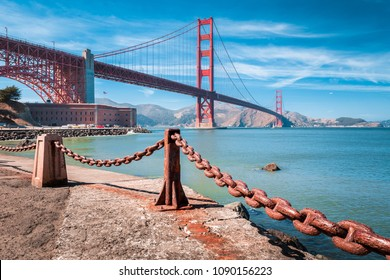 Classic view of famous Golden Gate Bridge with Fort Point National Historic Site on a beautiful sunny day with blue sky and clouds, San Francisco, USA