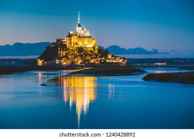 Classic view of famous Le Mont Saint-Michel tidal island in beautiful twilight during blue hour at dusk, Normandy, northern France