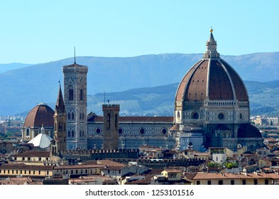 The classic view of Florence of the Duomo, Campanille and Baptistry, as seen from the Piazzale Michelangelo. Behind the city rise the hills of Fllorence, to a clear blue sky.