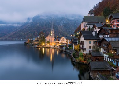 Classic view of Hallstatt with traditional houses and illuminated church at sunrise, Salzburger Land, Austria