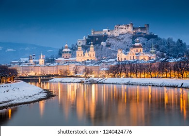 Classic view of the historic city of Salzburg with famous Festung Hohensalzburg and Salzach river illuminated in beautiful twilight during scenic Christmas time in winter, Salzburger Land, Austria