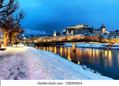 Classic view of the historic city of Salzburg with Salzburg Cathedral and famous Festung Hohensalzburg illuminated in winter, Salzburger Land, Austria