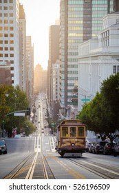 Classic view of historic old cable car on famous California Street with Oakland Bay Bridge in the background in beautiful golden morning light at sunrise in summer, San Francisco, California, USA