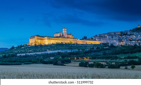 Classic view of the historic town of Assisi illuminated in beautiful twilight during blue hour at dusk in summer, Umbria, Italy