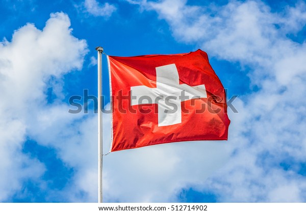 Klassische Sicht auf die Nationalflagge der Schweiz, die an einem sonnigen Sommertag am 1. August, dem Nationalfeiertag der Schweizerischen Eidgenossenschaft, im Wind gegen blauen Himmel und Wolken weht