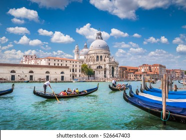 Classic view of traditional Gondolas on Canal Grande with historic Basilica di Santa Maria della Salute in the background on a beautiful sunny day with blue sky and clouds in summer in Venice, Italy