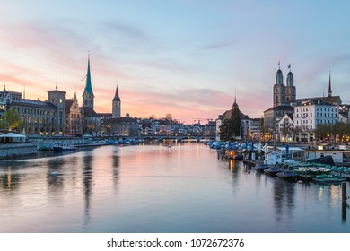Classic views of the Zurich skyline at long the Limmat river at sunset. The Grossmunster, Fraumunster and St. Peter Church can be seen.