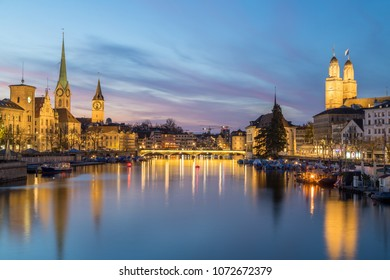 Classic views of the Zurich skyline at long the Limmat river at sunset and into the blue hour. The Grossmunster, Fraumunster and St. Peter Church can be seen.