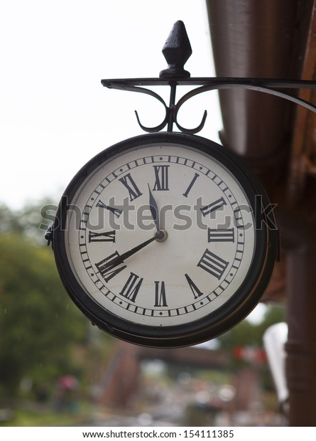 Classic vintage clock at old railway station with rain on clock face