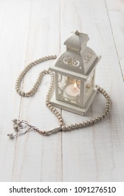 Classic vintage white color candle holder or decorative lantern with prayer beads. Religious object and background.