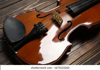 Classic violin on wooden background, closeup view