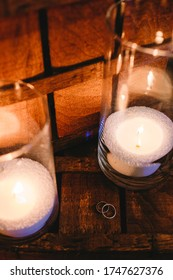 Classic wedding rings with candles . Candle light. Good photo of wedding detail. Shallow focus and some noise.