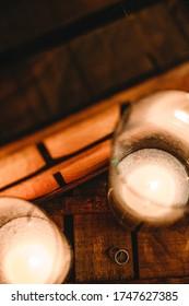 Klassische Hochzeitsringe mit Kerzen . Kerzenlicht. Gutes Foto von Hochzeitsdetails. Schmaler Fokus und etwas Rauschen.