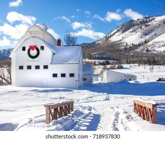 Classic white barn in mountains surrounded by snow on a sunny winter day.