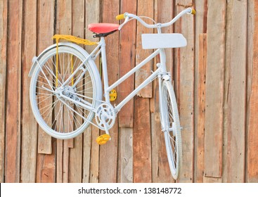 classic white bicycle hanging on old wooden wall and white plate.