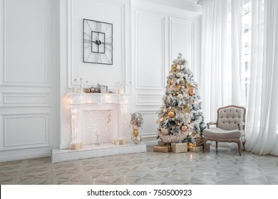 Classic white christmas interior with new year tree decorated. Fireplace with grey chair, clocks on the wall and presents under the tree