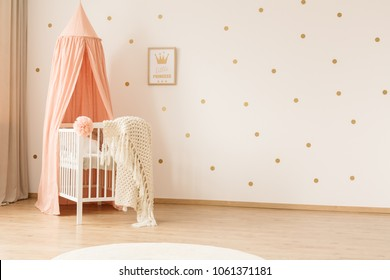 Classic white crib with a peach pink canopy in a girly nursery bedroom interior with gold polka dots on the wall and copy space