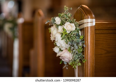Classic white floral arrangement of flowers for church wedding celebration with pews