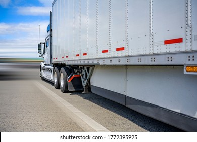 Classic white powerful long haul diesel big rig semi truck with high cab transporting cargo in dry van semi trailer with aerodynamic skirt running on the wide straight road to point of delivery