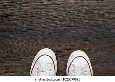 classic white sneaker on wooden