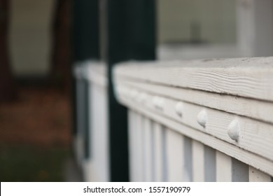 classic white wooden banister on a frontporch with small focus point