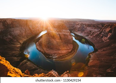 Classic wide-angle view of famous Horseshoe Bend, a horseshoe-shaped meander of the Colorado River located near the town of Page, in beautiful golden evening light at sunset in summer, Arizona, USA