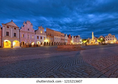 Classic wide-angle view of main square of Telc with renaissance and baroque colorful houses. Public fountain with statue of st. Margaret and Plague Column. Summer evening with dramatic sky.