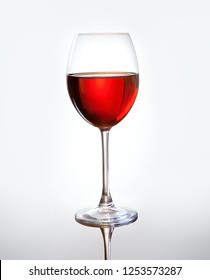 Classic wineglass with red wine over light gray background