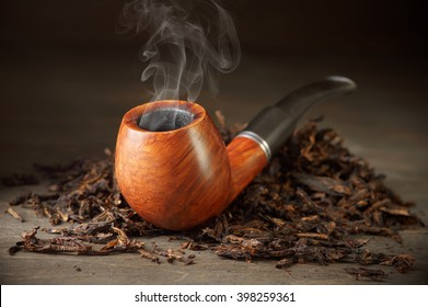 Classic wooden pipe with smoke and tobacco pile on vintage wood.