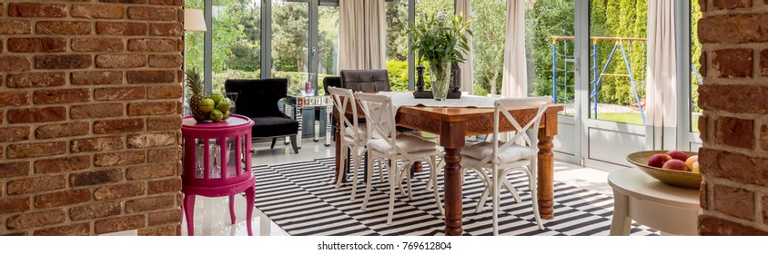 Classic wooden table and white chair on patterned carpet in eclectic dining room with pink cabinet