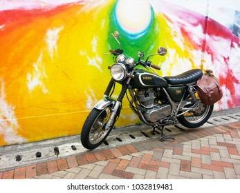 A classic Yamaha SR  motorcycle (Yamaha celebrates 35 years of glorious SR production) with a pannier bags on colorful wall background at Kowloon in Hong Kong on 25 Feb 2018