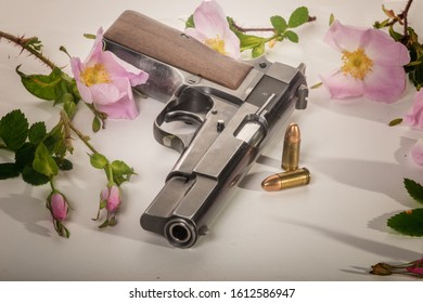 Classical 9mm semi-automatic pistol with cartridges - presentation in a bed of wild roses.
