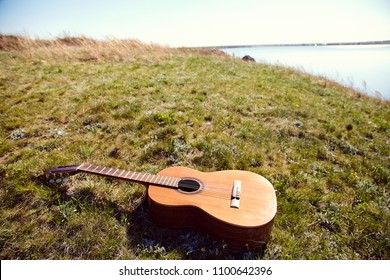 classical acoustic guitar lying on the grass summer outdoors