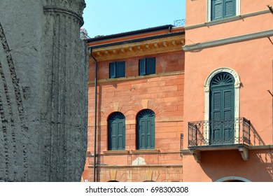 Classical and ancient Italian buildings with red facade and green window shutters