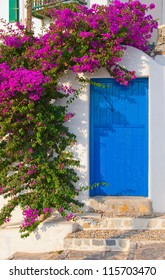 The classical architecture of the Greek cities - with its narrow streets, blue door on the white buildings and flowers at the entrance!