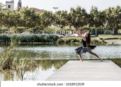 Classical ballerina posing on a footbridge of an urban lake on a sunny day